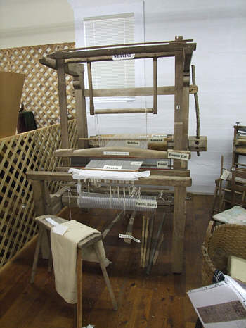 This loom, from the weaving cabin, is on display in our museum.